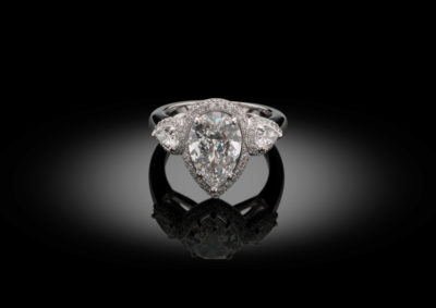 Exceptional trilogy ring with pear shaped diamonds, finished with a double diamond entourage.