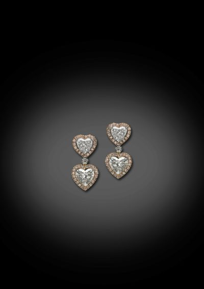 'Toi & Moi' styled heart shape diamonds earrings, finished with an entourage in pink diamonds.